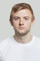 Portrait of serious young man in t_shirt against gray background