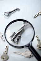 A key lying amongst many being magnified by a magnifying glass