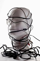 A white mannequin bust entangled in various cords and cables