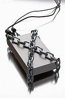 A thick metal chain wrapped around an external hard drive