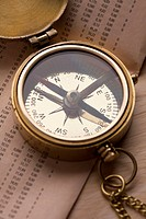 A brass pocket compass on top of the financial page of a newspaper