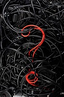 A single red cord in the form of a question mark amongst a tangle of black cords and cables