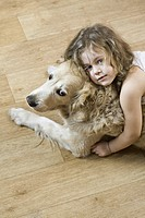 A young girl hugging a dog