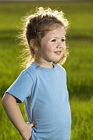 A young girl standing in a field and looking away