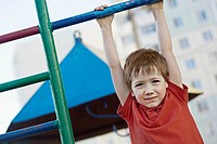 A boy hanging from a playground bar