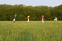 Children walking in a field with balloons