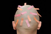 Adhesive tabs on the head of a man, rear view