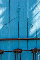 A wire coat hanger on a blue wall