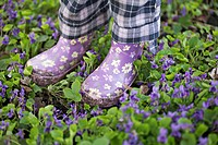 Low section of a girl standing in a garden with gumboots