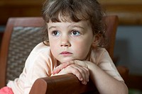 A young girl sitting on a chair and looking away