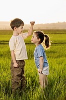 A boy and a girl in a field comparing heights