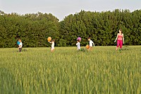 A woman standing in a field with four children