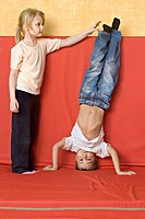 A girl standing next to a boy doing a headstand