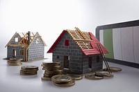 Two partially constructed models of a house with piles of European Union coins around them