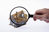 A human hand holding a magnifying glass up to a partially constructed miniature house model