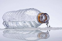A plastic water bottle lying on its side, water spilling out (thumbnail)