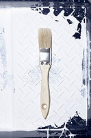 A clean house painting brush lying in a used paint tray with old paint on it (thumbnail)