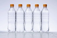 A row of five full plastic water bottles in a row (thumbnail)