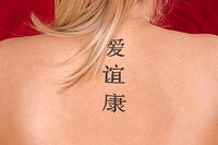 A woman tattoos of Chinese characters meaning Love, Friendship and Health