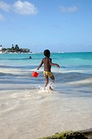A young boy running towards the sea holding a sand pail