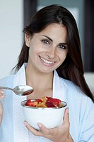 Woman with breakfast bowl of cereal and strawberries