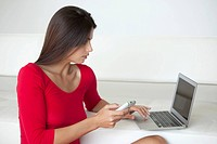 Woman in red using phone and laptop