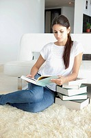 Woman at home leaning on books and reading