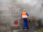 Worker removing graffiti with pressure hose