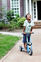 A carefree boy laughing while riding a push scooter
