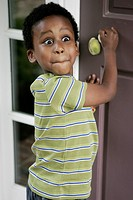 A boy with a surprised expression standing at the front door or his house