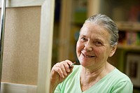 A cheerful senior woman holding a paintbrush