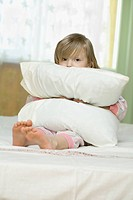 A little girl looking sad while squeezing a pillow