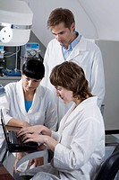 Two lab technicians watching as a third tech types notes on a laptop