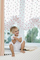 A young girl sitting on a window sill, clapping hands excitedly