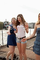 Three female friends looking at bubbles on the Spree River, Berlin, Germany