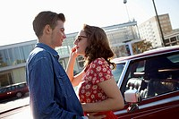 A rockabilly couple standing face to face next to a vintage car