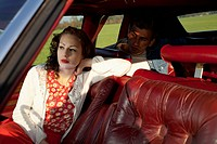 A rockabilly woman and man sitting in a vintage car (thumbnail)