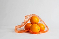 A pile of oranges in an open net bag