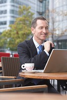 Businessman working on laptop at cafe