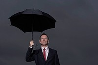 Businessman standing under umbrella
