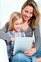Mother and daughter using electronic tab