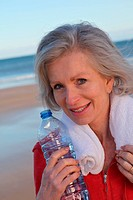 Active senior woman drinking water from bottle at the beach