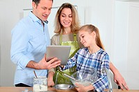 Parents and daughter preparing meal in home kitchen