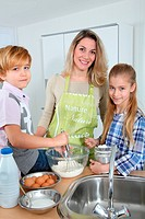 Mother and children in kitchen preparing cake