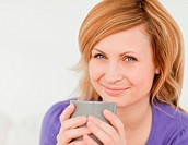 Portrait of a good looking red_haired woman holding a cup of cof