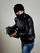 Portrait of male burglar with a handbag.