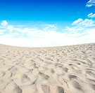 Sand and sky with clouds and sun background