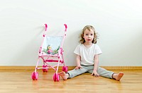 Little cute girl sitting on the floor next to the toy stroller