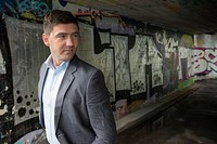 Portrait of a businessman in a walkway covered with grafitti