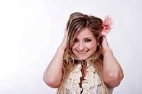 Junge blonde Frau legt lachend die Hände auf die Ohren